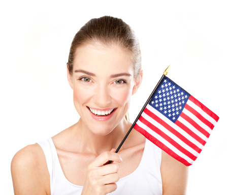 Beautiful smiling young woman holding small American flag.
