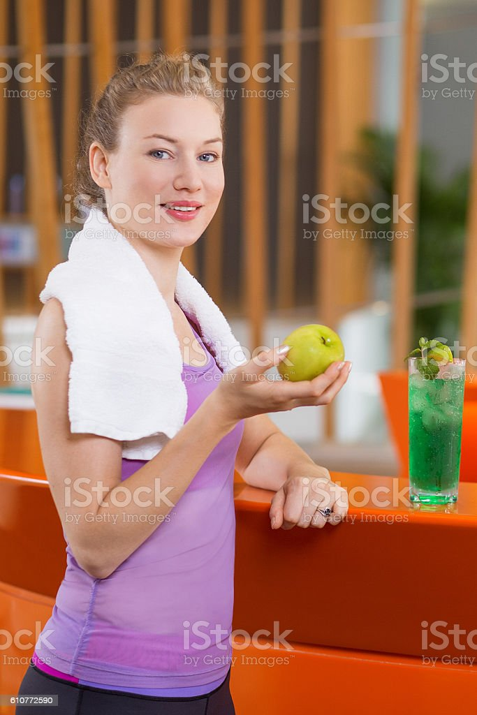 Smiling Young Woman with Apple in Sport Bar stock photo
