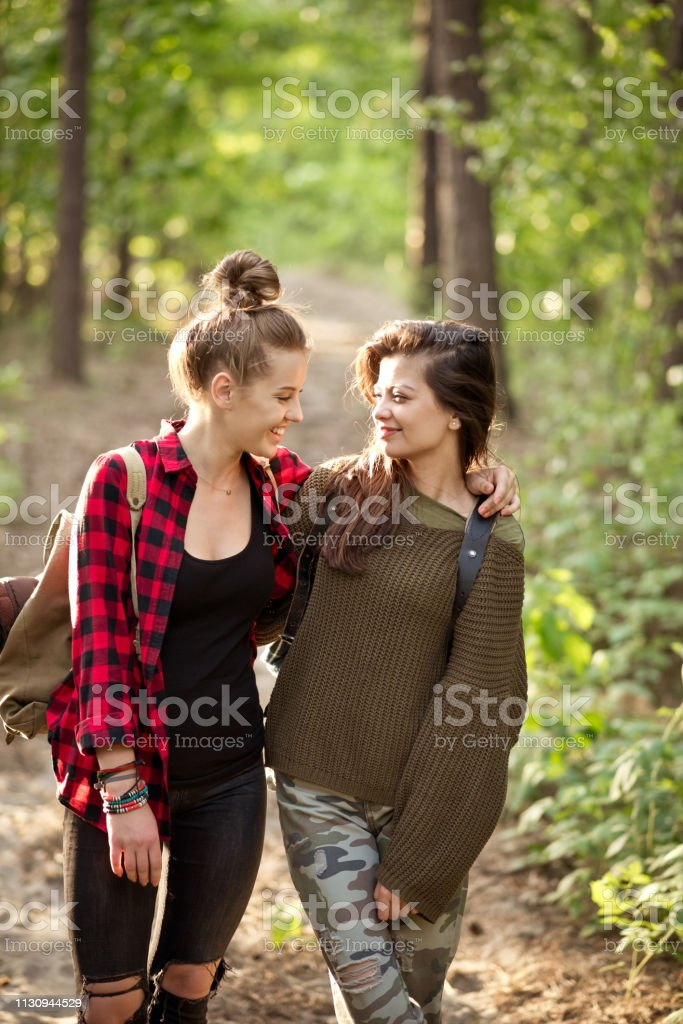 Smiling young woman with arm around on friend Smiling beautiful young hikers standing on footpath. Happy female hipster is with arm around on friend. They are spending weekend in forest. 20-24 Years Stock Photo