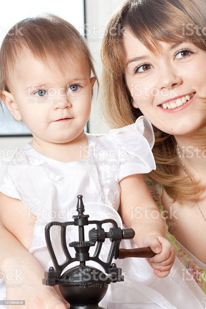 Smiling Young Woman with Coffee Grinder and baby royalty-free stock photo