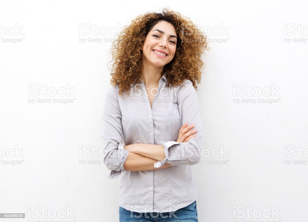smiling young woman with curly hair against white background – zdjęcie