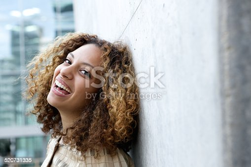 istock Smiling young woman with curly hair 520731335