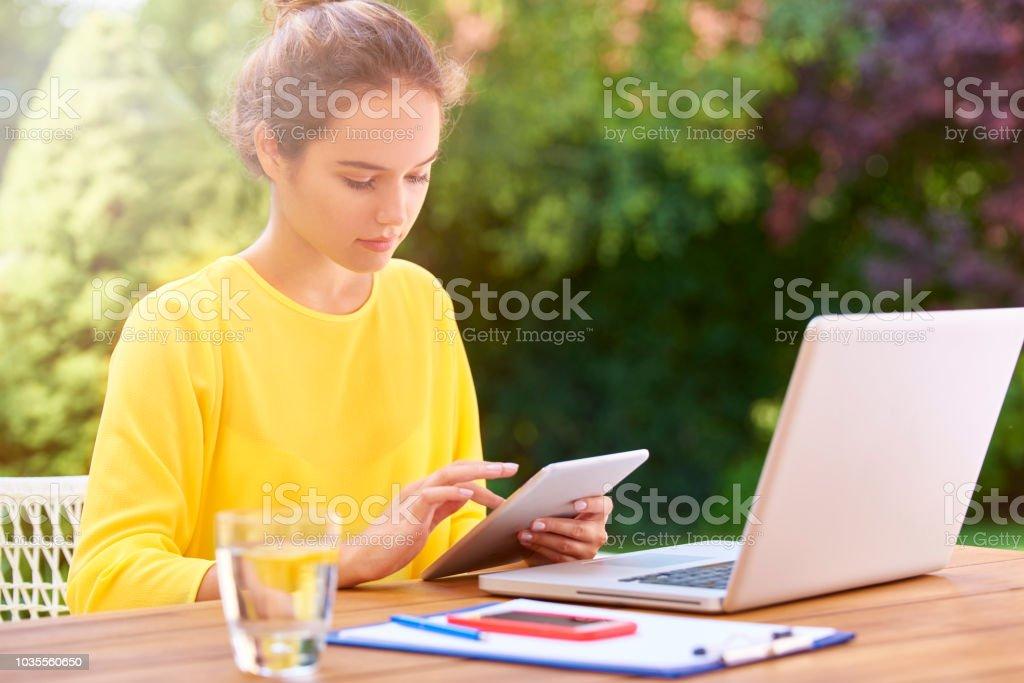Souriante jeune femme avec tablette numérique et ordinateur portable - Photo