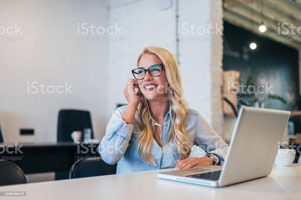 Lächelnde junge Frau mit Kopfhörer sitzt vor einem Laptop. – Foto