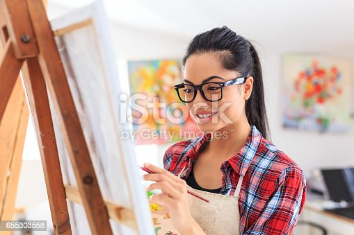 istock Smiling young woman with eyeglasses drawing 655303558