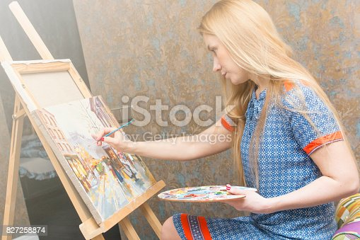 istock Smiling young woman with eyeglasses drawing 827258874