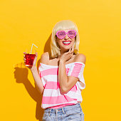 Smiling blond young woman in pink sunglasses holding red drink. Waist up studio shot on yellow background.