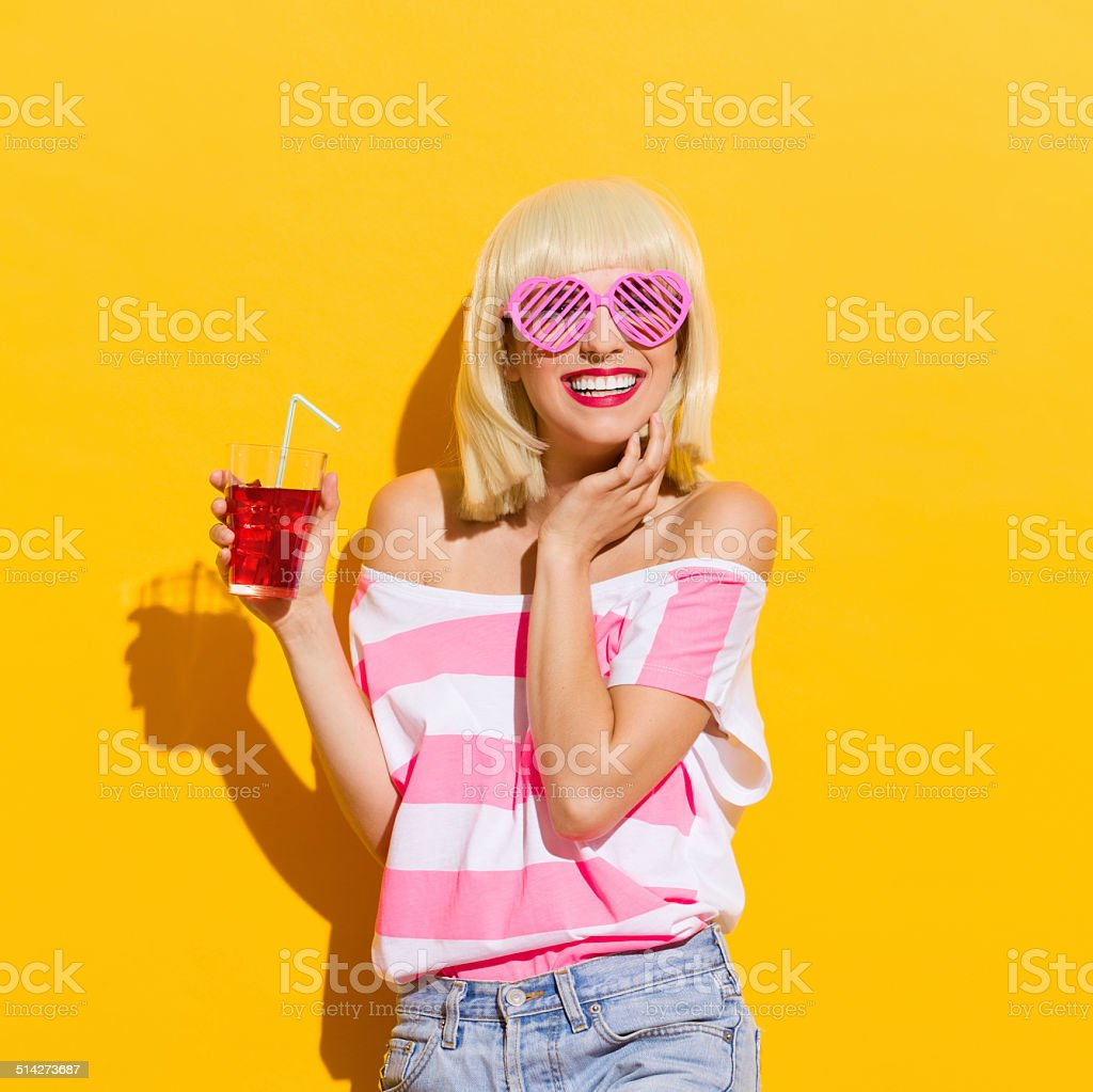 Smiling young woman with fresh red drink stock photo
