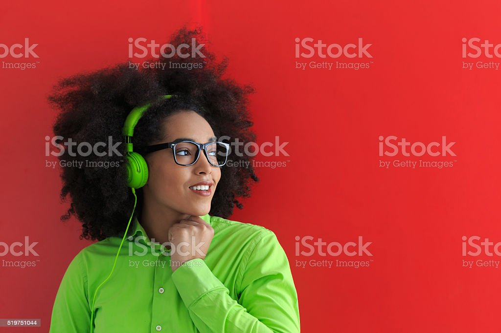 Smiling young woman with green headset listening music stock photo