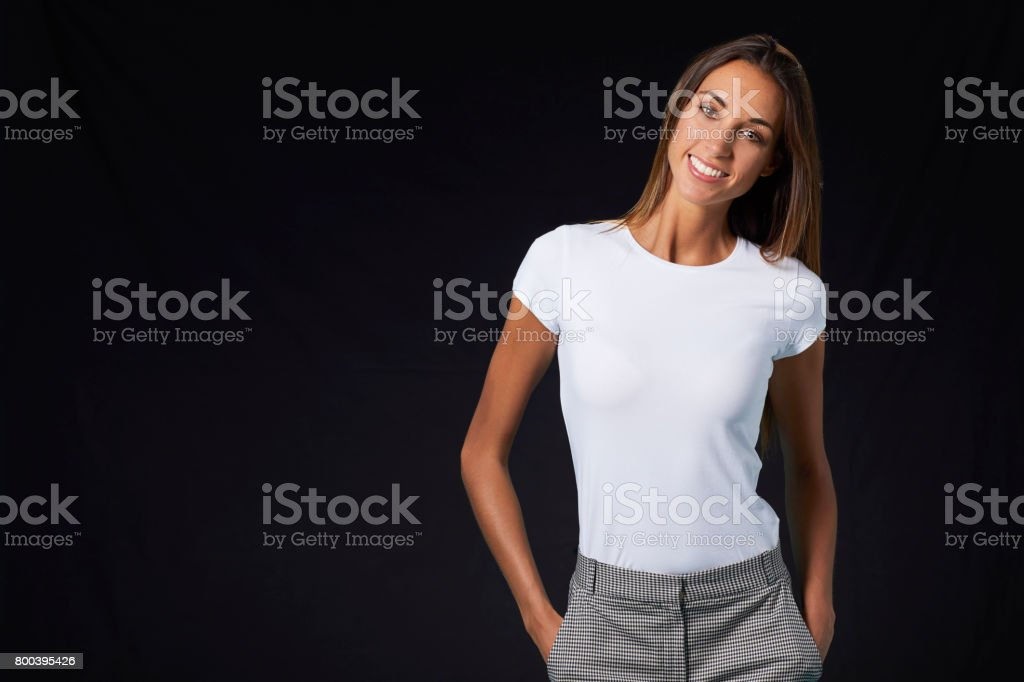 Smiling young woman with hands in pockets stock photo
