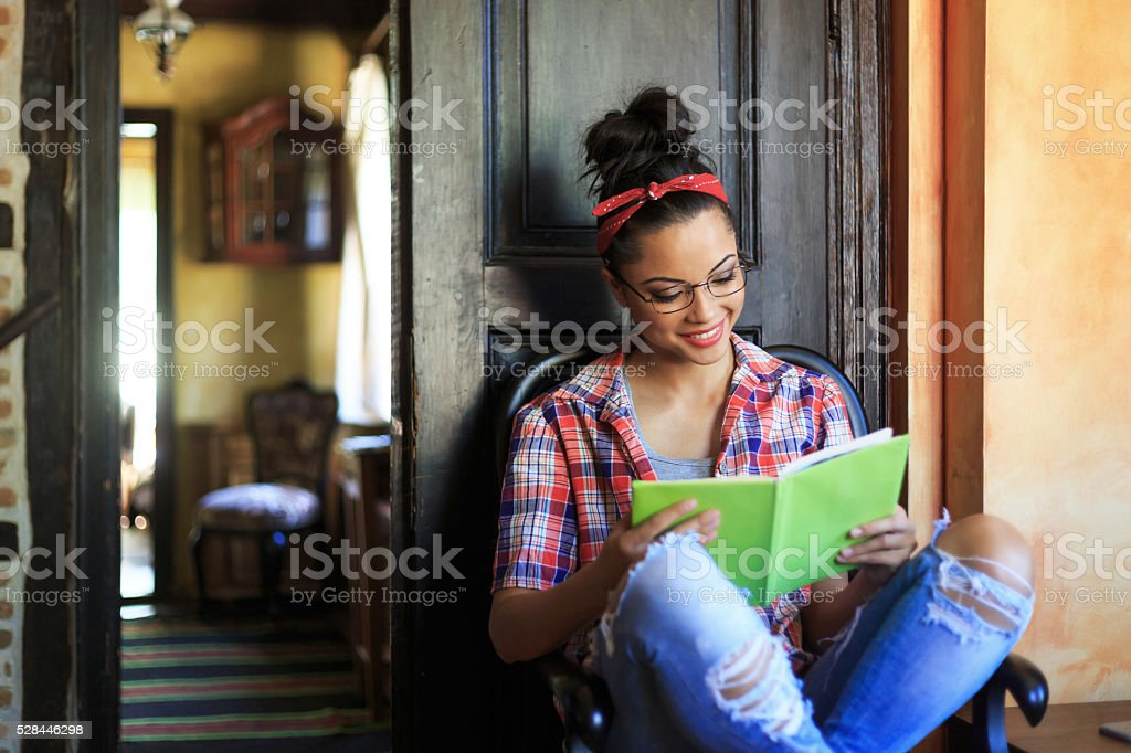 Smiling young woman with headband reading a book stock photo