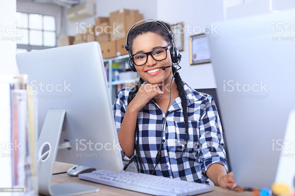 Smiling young woman with headset sitting on workplace stock photo