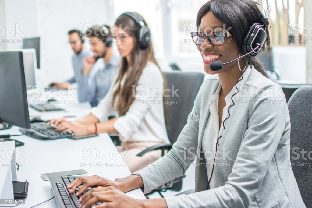 Joven sonriente con auriculares trabajando en call center. - foto de stock
