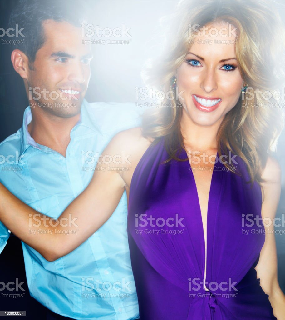 Smiling young woman with her boyfriend dancing in a club royalty-free stock photo