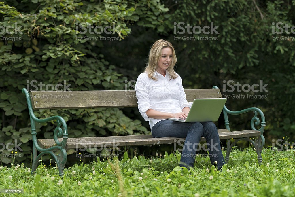 smiling young woman with laptop on park bench royalty-free stock photo