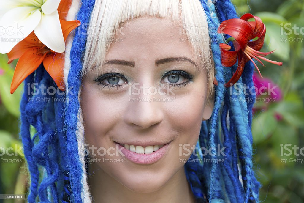 Smiling young woman with lilies in dreadlocks. royalty-free stock photo