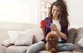 Happy girl with smartphone and dog at home. Curly woman messaging online on couch with her puppy, copy space