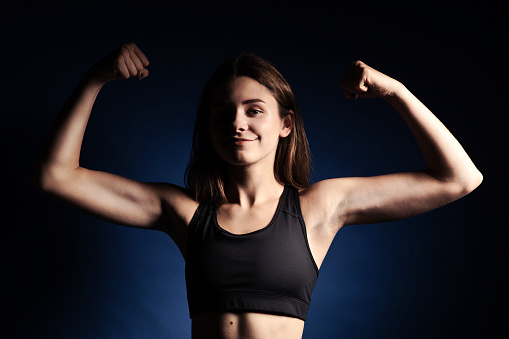657442382 istock photo smiling young woman with muscles 1142862050