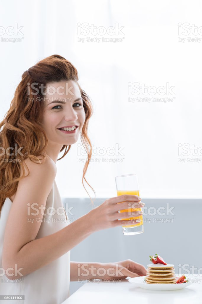 smiling young woman with orange juice and pancakes with strawberry for breakfast looking at camera stock photo