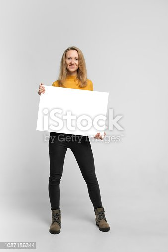 istock Smiling young woman with poster 1087186344