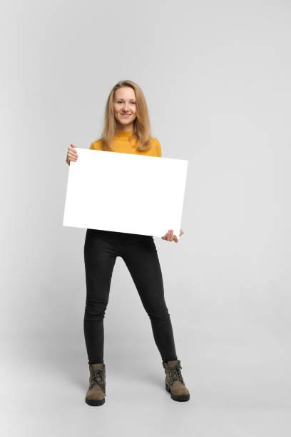 微笑的年輕婦女與海報 - 標誌 個照片及圖片檔