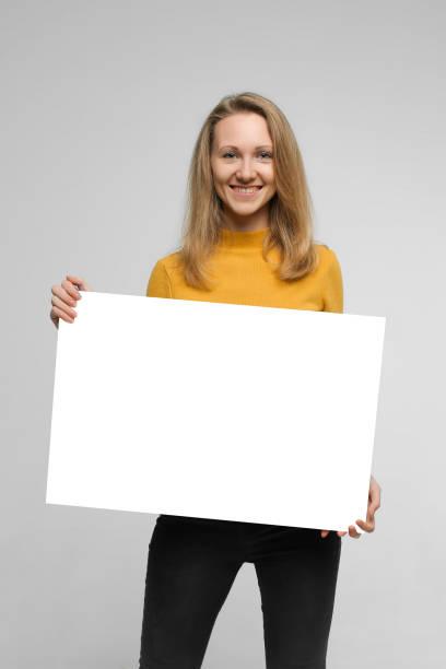 lachende jonge vrouw met poster - zwarte spijkerbroek stockfoto's en -beelden
