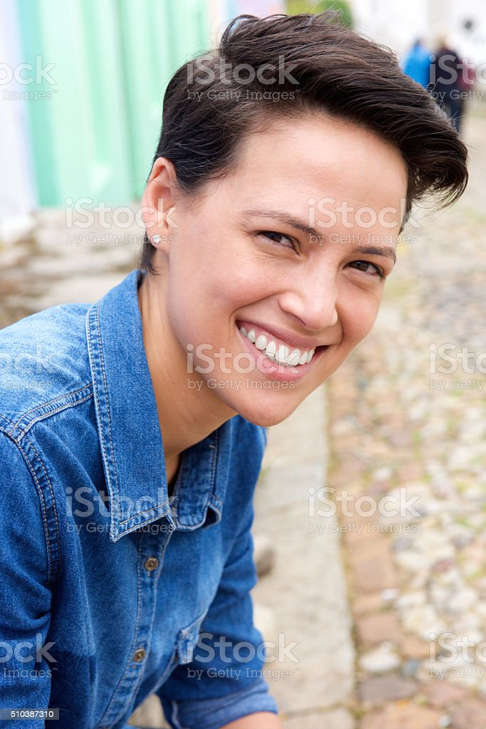 Smiling young woman with short hair stock photo