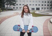 Young smiling beautiful woman with skateboard and headphones in park on cold autumn day