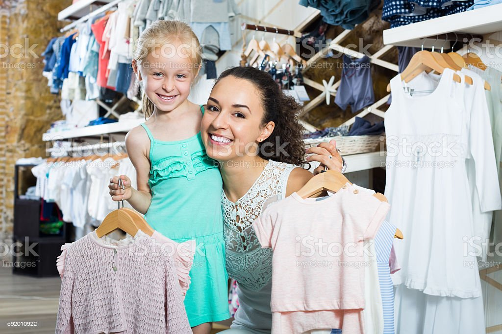 Smiling young woman with small girl holding clothes stock photo