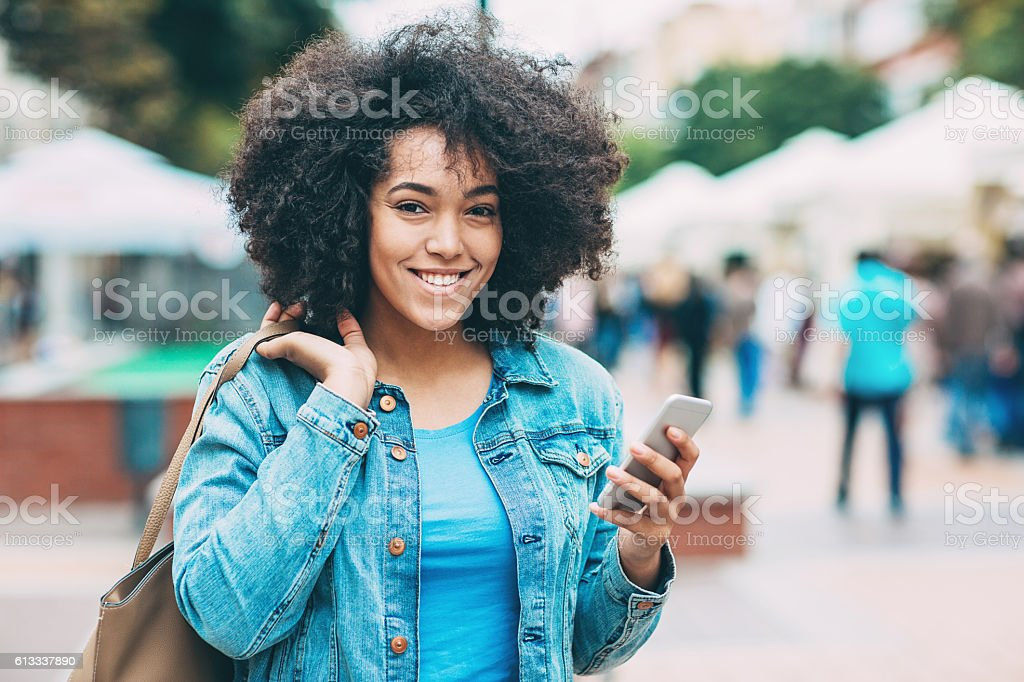 Smiling young woman with smart phone stock photo