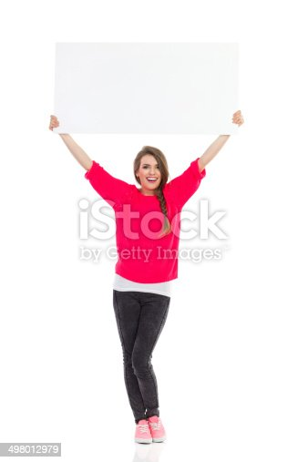 istock Smiling young woman with white placard 498012979
