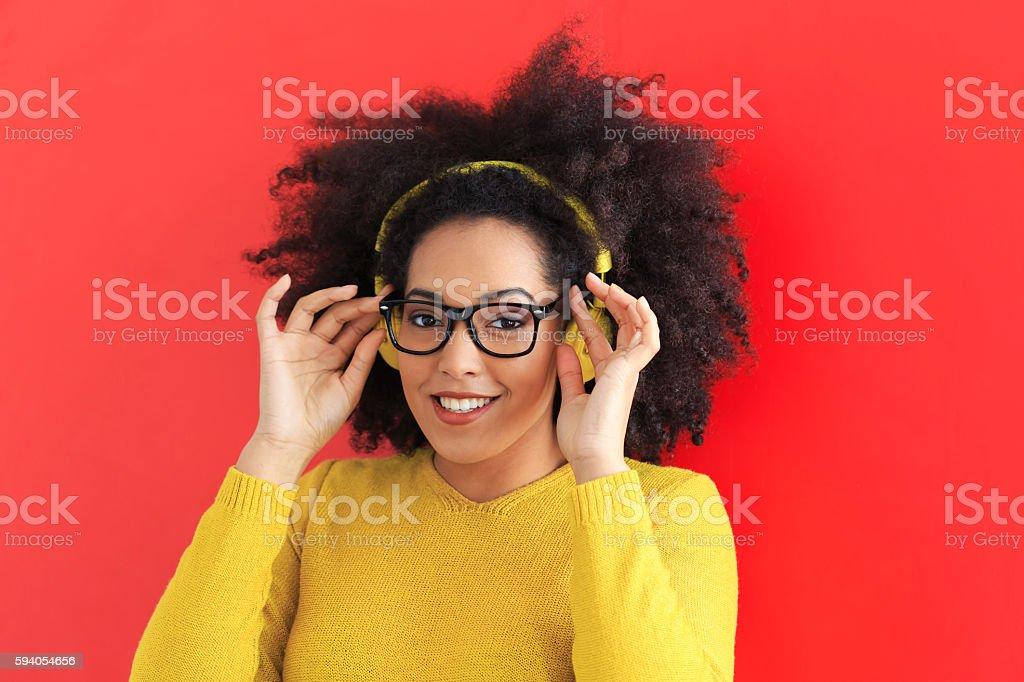 Smiling young woman with yellow headphones and eyeglasses stock photo
