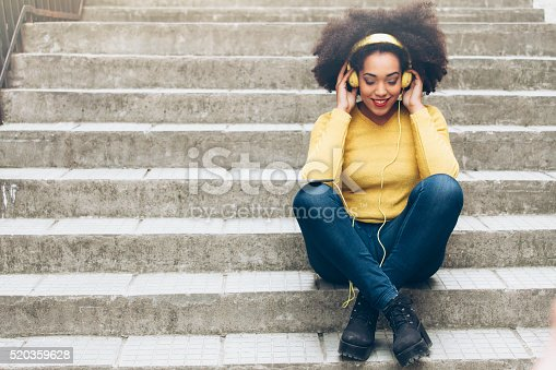 istock Smiling young woman with yellow headphones sitting on stairs 520359628