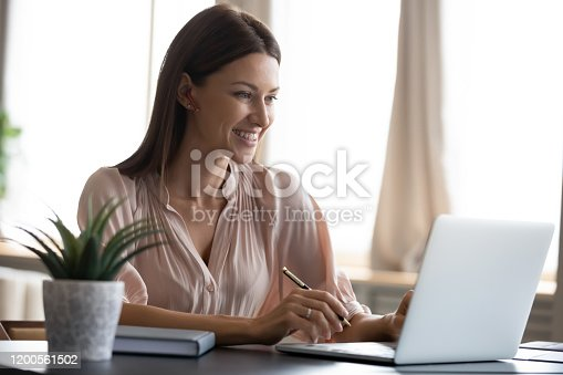 Smiling young woman wearing headphones sit at desk working at laptop making notes, happy millennial female in modern earphones study watch webinar on computer handwrite in notebook
