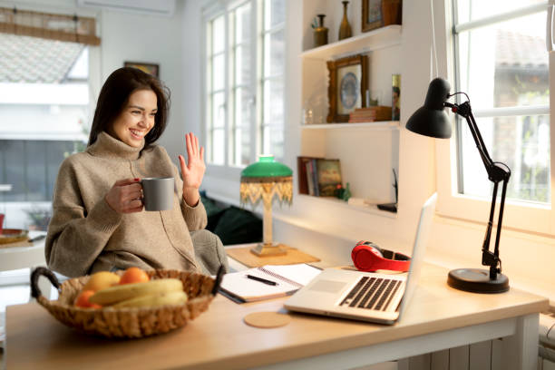 Smiling young woman working from home on a laptop stock photo