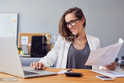 istock Smiling young woman working in home office using laptop and documents 1030227584