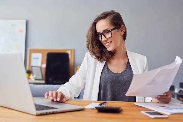 Smiling young woman working in home office using laptop and documents Smiling young woman working in home office using laptop and documents accounting ledger stock pictures, royalty-free photos & images