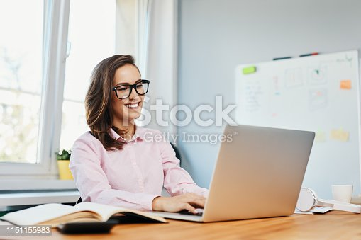 Smiling young woman working in office with laptop