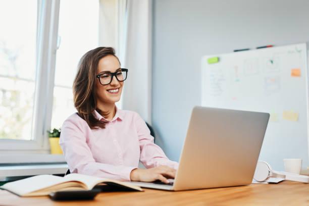 Lächelnde junge Frau, die im Büro mit Laptop arbeitet – Foto