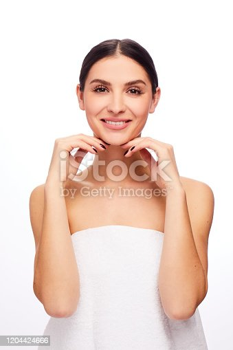 Studio portrait of a smiling young brunette woman with perfect skin wrapped in a towel and touching her chin against a white background