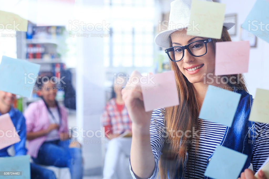 Smiling young woman writing on sticky notes stock photo
