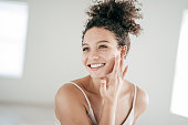 Smiling young women applying moisturiser to her face