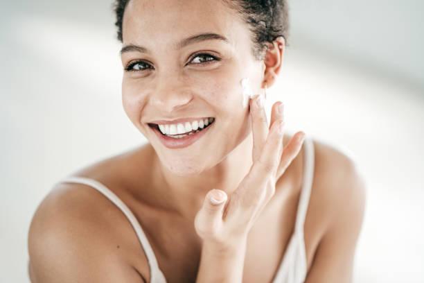 Lächelnde junge Frauen, die Feuchtigkeitsbefeuchter auf ihr Gesicht auftragen – Foto