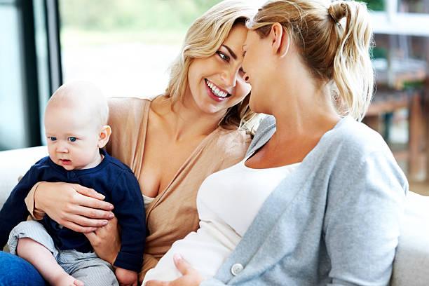 Sonriente Joven mujer con niño pequeño de estar - foto de stock