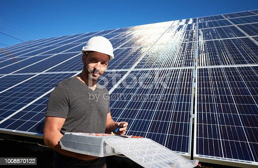 istock smiling young worker keeping equipment standing near solar panels. 1008870122