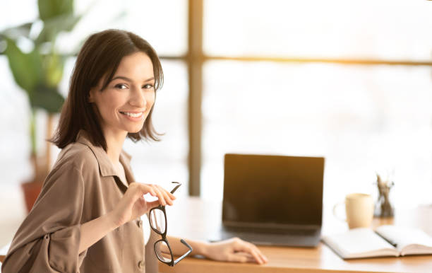 Smiling young worker with blank screen laptop stock photo