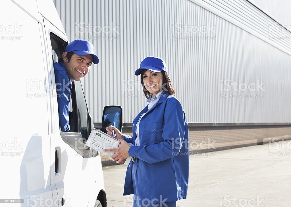Smiling young workers outside warehouse royalty-free stock photo
