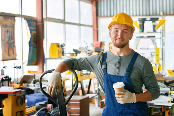smiling young workman on break - manufacturing occupation stock photos and pictures