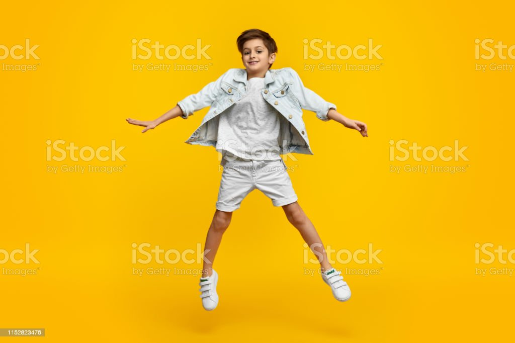 Lächelnde Jugendliche im stylischen Outfit springen auf - Lizenzfrei Ausgestreckte Arme Stock-Foto