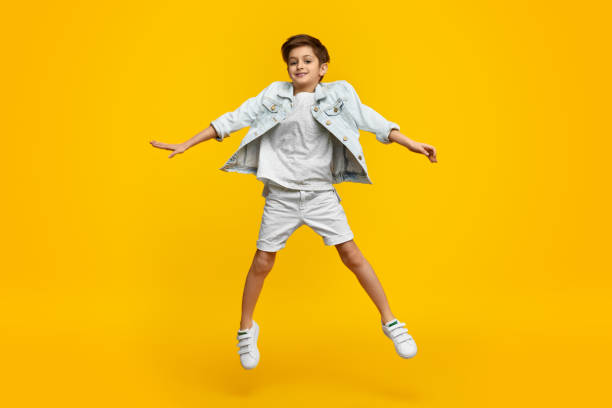 Smiling youngster in stylish outfit leaping up stock photo